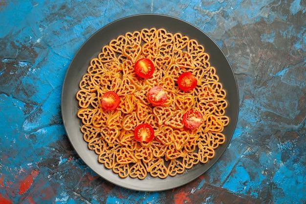 Bovenaanzicht italiaanse pastaharten gesneden kerstomaatjes op zwarte ovale plaat op blauwe tafel