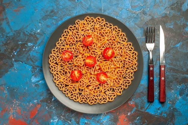Bovenaanzicht italiaanse pastaharten gesneden kerstomaatjes op zwarte ovale plaatvork en mes op blauwe tafel