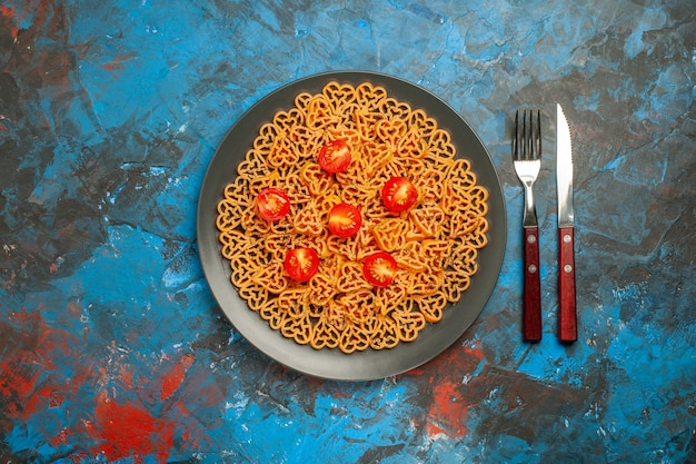 Bovenaanzicht italiaanse pastaharten gesneden kerstomaatjes op zwarte ovale plaatvork en mes op blauwe tafelkopieplaats