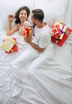 Bovenaanzicht jong koppel in santa hoeden zittend in bed