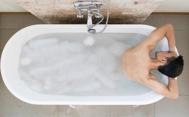 Bovenaanzicht jonge aziatische man ontspannen en spa in badkuip