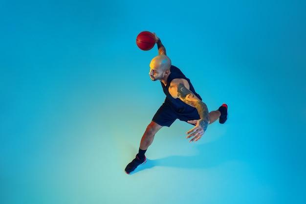 Bovenaanzicht. jonge basketbalspeler van team die sportkleding draagt, oefent in actie, beweging op blauwe achtergrond in neonlicht. concept van sport, beweging, energie en dynamische, gezonde levensstijl.
