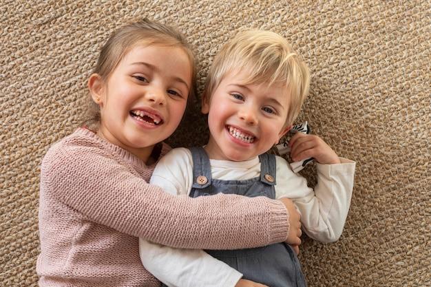 Bovenaanzicht jonge broers en zussen knuffelen