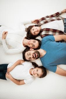 Bovenaanzicht jonge en gelukkige familie liggend op matras