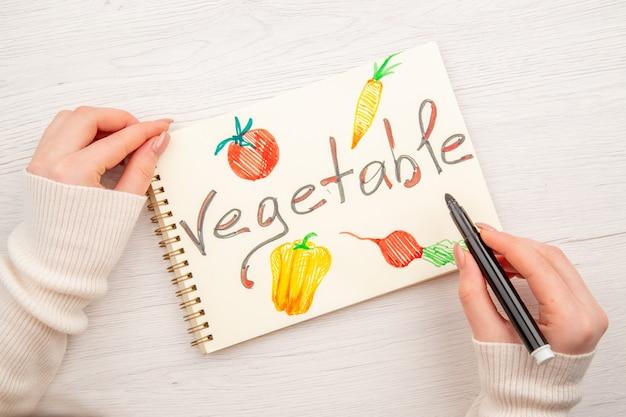 Bovenaanzicht jonge vrouw schrijven en tekenen op kladblok op wit bureau