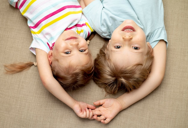 Bovenaanzicht jongen en meisje, zittend op de vloer