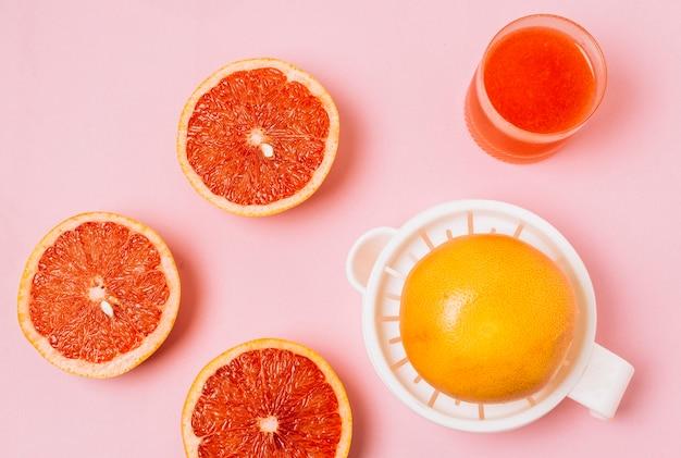 Bovenaanzicht juicer naast gehalveerde grapefruits