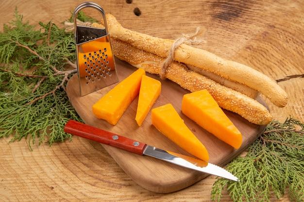 Bovenaanzicht kaas- en broodmes kleine doosrasp op snijplank pijnboomtakken