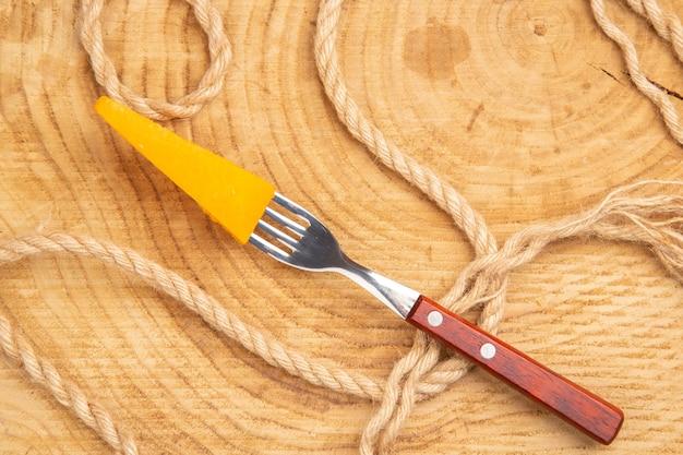 Bovenaanzicht kaas op vork touw op houten tafel