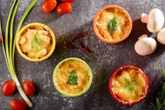 Bovenaanzicht kaas ovenschotel met champignons in kleurrijke kokosnoten, rode kerstomaatjes op grijze achtergrond, gratin concept