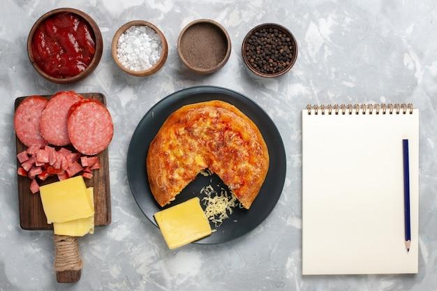 Bovenaanzicht kaas pizza met verschillende kruiden op wit bureau