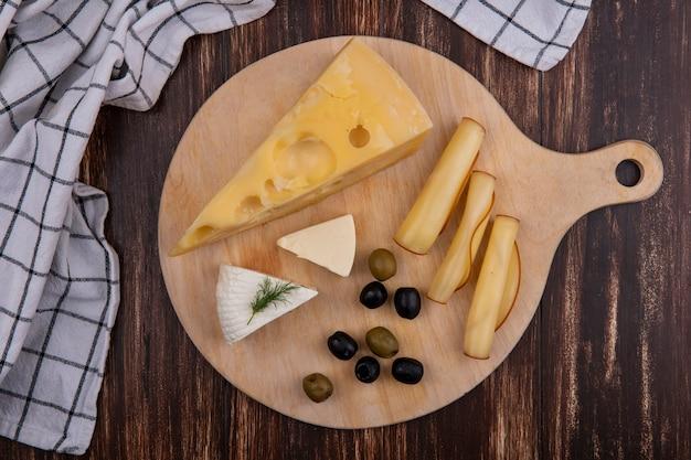 Bovenaanzicht kaasvariëteiten met olijven op een standaard met een geruite handdoek op een houten achtergrond