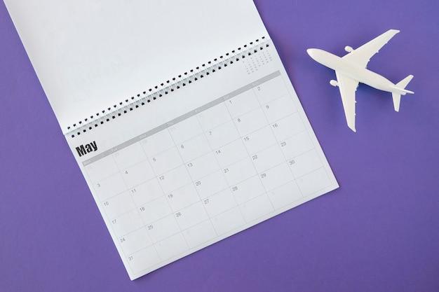 Bovenaanzicht kalender en wit speelgoed vliegtuig