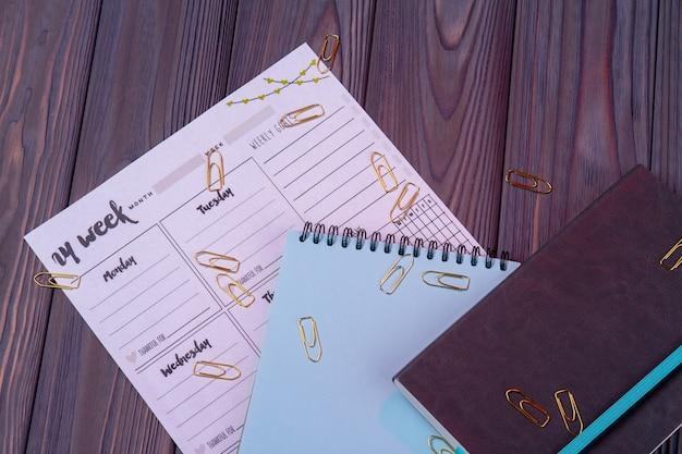 Bovenaanzicht kalender met kladblok en voorbeeldenboek. briefpapieraccessoires op donker houten bureau.