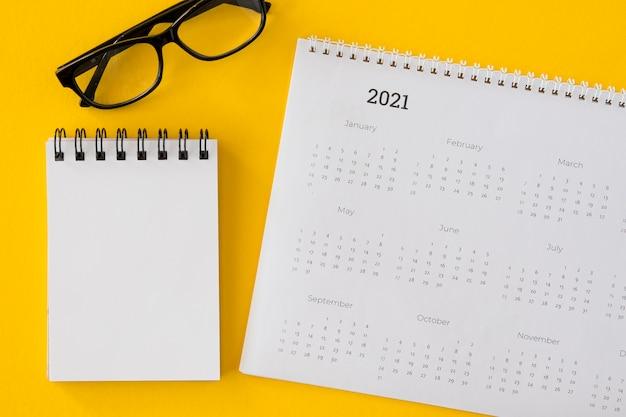 Bovenaanzicht kalender met notitieblok en bril