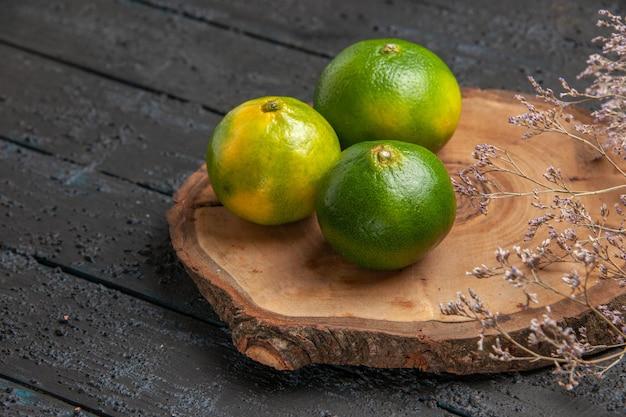 Bovenaanzicht kalk op tafel limoenen op bruin bord op de grijze tafel onder takken van boom