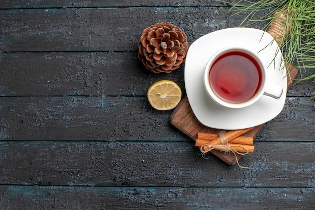Bovenaanzicht kaneelstokjes kaneelstokjes citroen en kegel naast het kopje thee en kerstboomtakken
