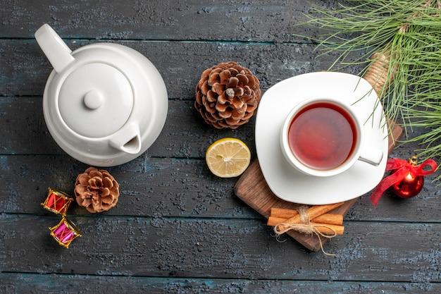 Bovenaanzicht kaneelstokjes kaneelstokjes citroen en kegel naast het kopje thee theepot en kerstboomtakken met speelgoed