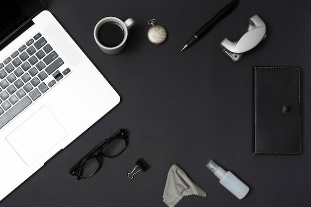 Bovenaanzicht kantoor spullen met laptop en een koffiekopje op zwarte tafel