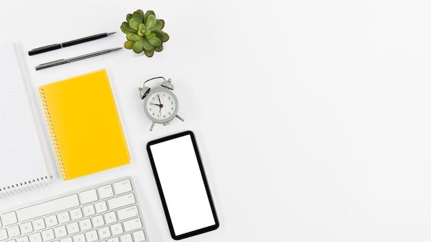 Bovenaanzicht kantoorbenodigdheden met mobiele telefoon en plant