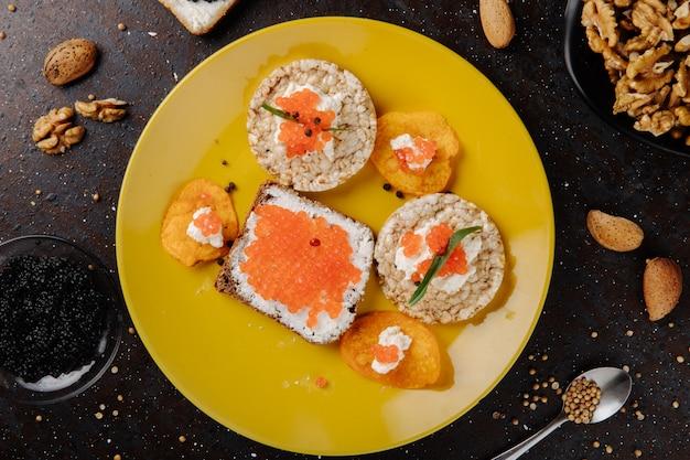 Bovenaanzicht kaviaar hapjes toast chips en knapperig knapperig brood met kwark rode kaviaar tarhun zwarte peper zwarte kaviaar amandel en walnoot