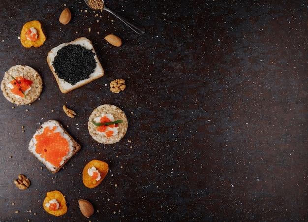 Bovenaanzicht kaviaar hapjes toast chips en knapperig knapperig brood met kwark rode kaviaar zwarte kaviaar tarhun amandel en walnoot aan de linkerkant met kopie ruimte op zwarte achtergrond