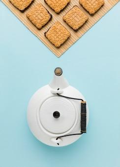 Bovenaanzicht keramiek theepot met zelfgemaakte koekjes