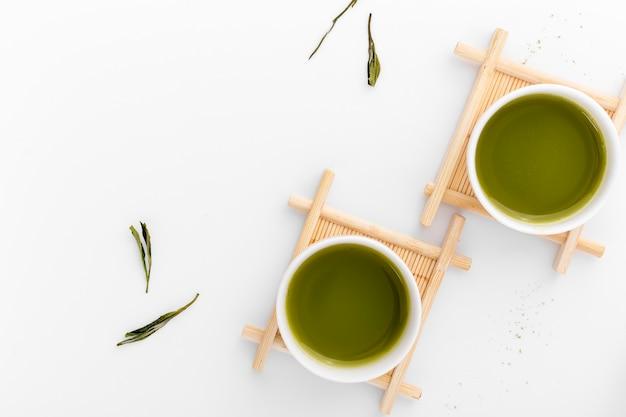 Bovenaanzicht keramische kopjes met matcha thee