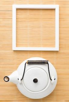 Bovenaanzicht keramische theepot en frame op de tafel