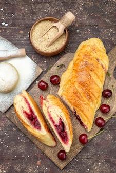 Bovenaanzicht kersen gebak heerlijk en zoet met verse zure kersen op het bruine houten bureau cake koekje suiker zoet bakken