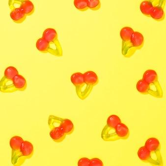 Bovenaanzicht kersen snoepjes op gele achtergrond