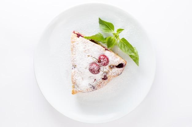 Bovenaanzicht kersencake plak heerlijk en lekker binnen witte plaat op de witte achtergrond cake koekje zoete suiker deeg bakken