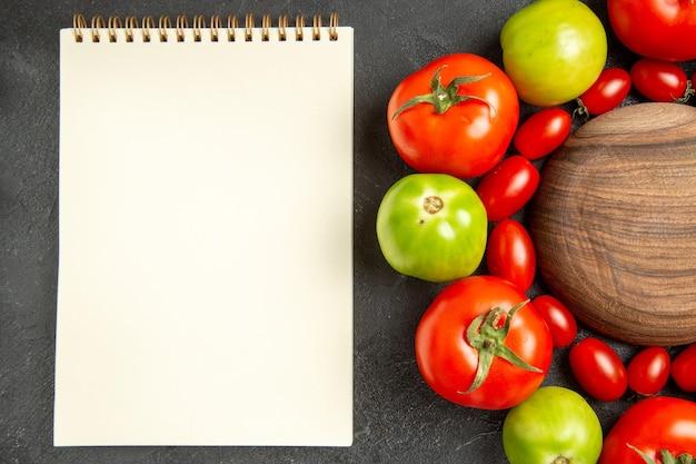 Bovenaanzicht kersenrode en groene tomaten rond een houten plaat en een notitieboekje op donkere grond