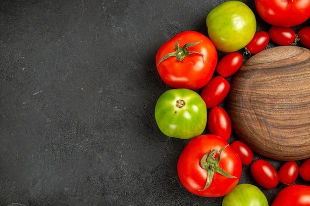 Bovenaanzicht kersenrode en groene tomaten rond een houten plaat op donkere tafel met vrije ruimte