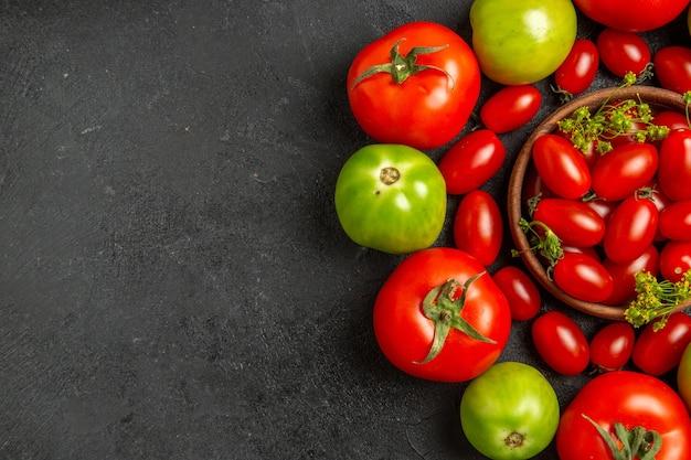 Bovenaanzicht kersenrode en groene tomaten rond een kom met kerstomaatjes en dillebloemen aan de rechterkant van donkere grond met vrije ruimte