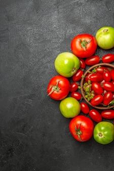 Bovenaanzicht kersenrode en groene tomaten rond een kom met kerstomaatjes en dillebloemen aan de rechterkant van het donkere oppervlak