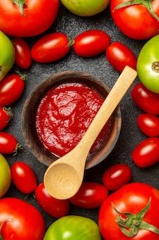 Bovenaanzicht kersenrode en groene tomaten rond een kom met ketchup en een houten lepel op donkere grond