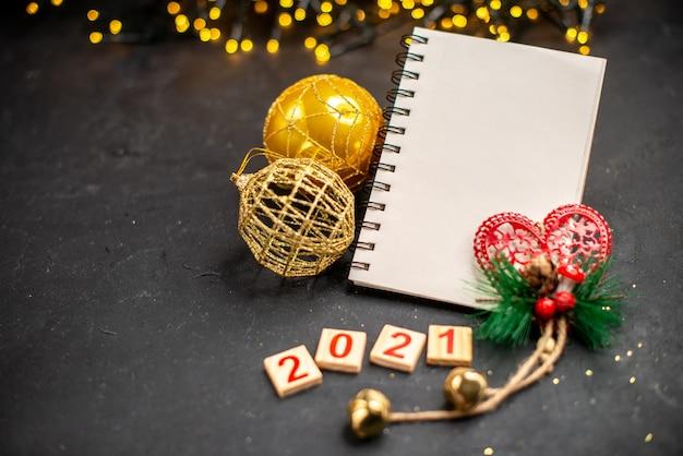 Bovenaanzicht kerst opknoping ornamenten een notebook hout blok kerstverlichting op donkere oppervlakte vrije ruimte
