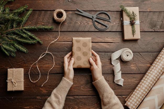 Bovenaanzicht kerstachtergrond met onherkenbare vrouw die geschenken inpakt aan houten tafel kopieerruimte