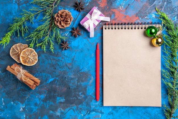 Bovenaanzicht kerstballen op een notebook pijnboomtakken kaneelstokjes anijs gedroogde citroen plakjes op blauwe ondergrond