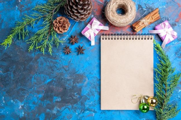 Bovenaanzicht kerstballen op een notebook pijnboomtakken kaneelstokjes anijs gedroogde citroen plakjes op blauwe oppervlak vrije plaats