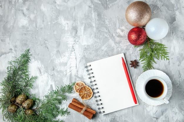 Bovenaanzicht kerstboom ballen notebook potlood kaneelstokjes kopje thee op grijze achtergrond kopie ruimte