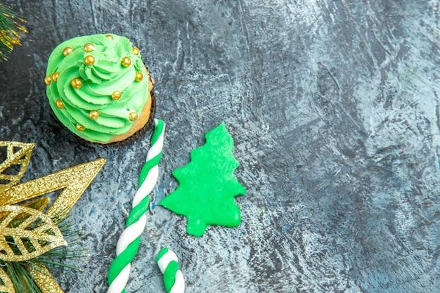 Bovenaanzicht kerstboom cupcake xmas candy xmas ornamenten op grijze ondergrond