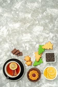 Bovenaanzicht kerstboom koekjes kopje thee kommen met chocolade en schijfjes citroen op grijze tafel kopie ruimte