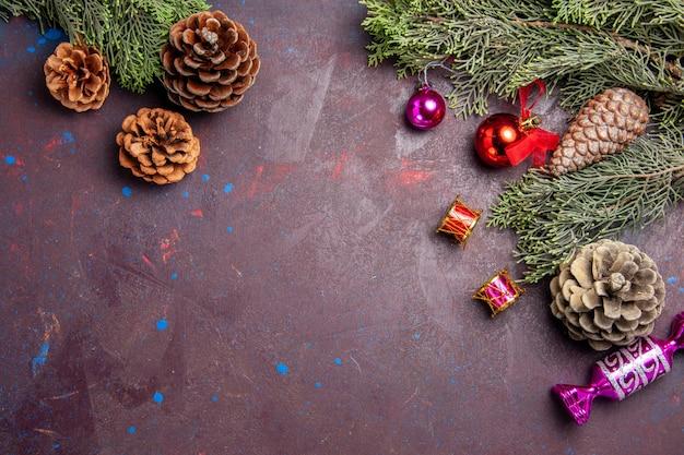 Bovenaanzicht kerstboom met kegels en speelgoed op donkere ruimte