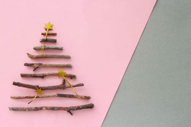Bovenaanzicht kerstboom silhouet gemaakt van houten takjes en op een pastel roze en grijze achtergrond met kopie ruimte