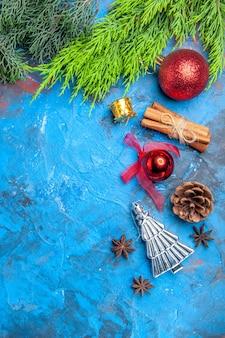 Bovenaanzicht kerstboom speelgoed anijs zaden kaneelstokjes op blauw-rood oppervlak