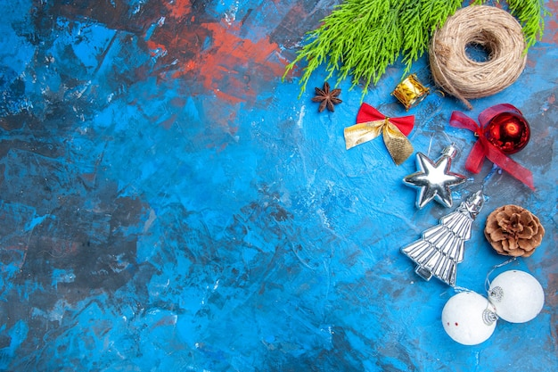 Bovenaanzicht kerstboom speelgoed stro draad anijs zaad op blauw-rode achtergrond met kopie plaats