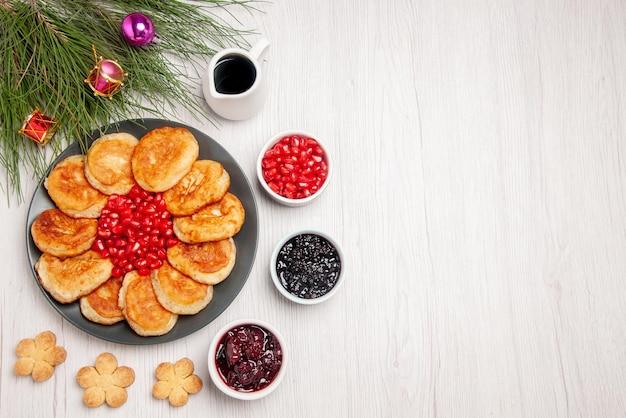 Bovenaanzicht kerstboomzaden van granaatappel en pannenkoeken in de plaat naast de kommen met bessenkoekjes en kerstboom met boomspeelgoed op tafel