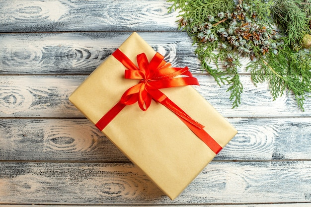 Bovenaanzicht kerstcadeau gebonden met rood lint dennenboomtakken op houten oppervlak